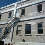 2nd & Wenatchee Ave, Exterior: Remove all failing paint, repair damaged concrete, prime all exposed concrete, prime and paint building in three colors.